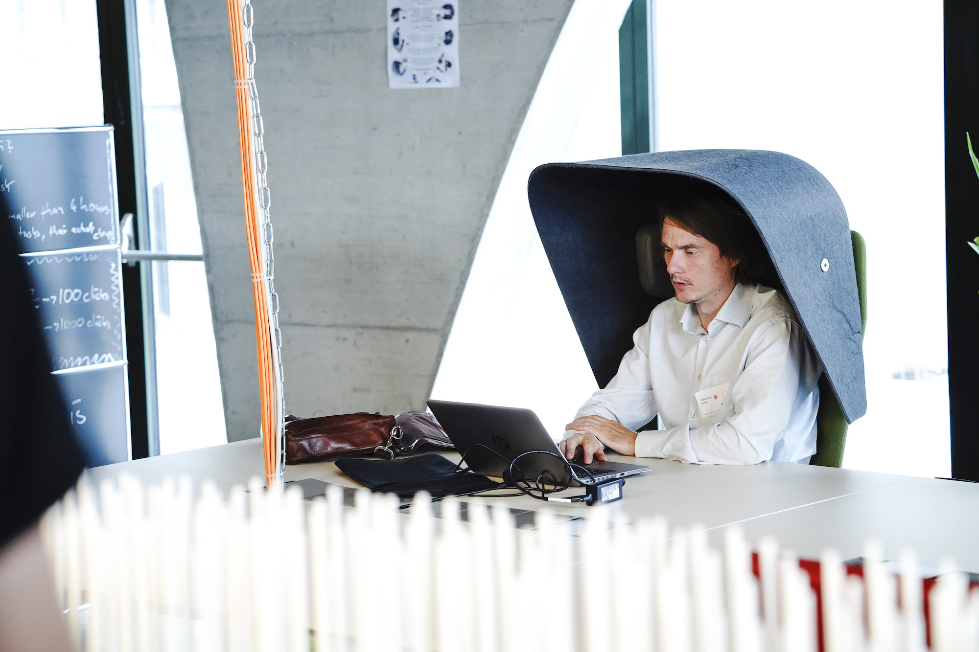 person working on laptop in a mobile acoustic chair