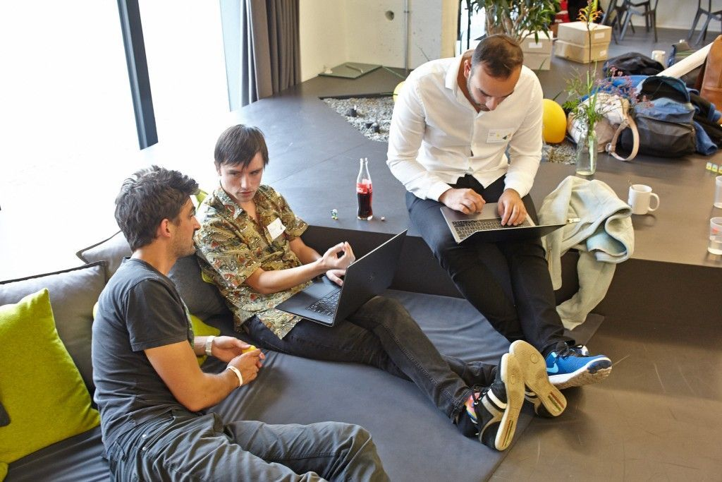 three men sitting on mats and working at laptops