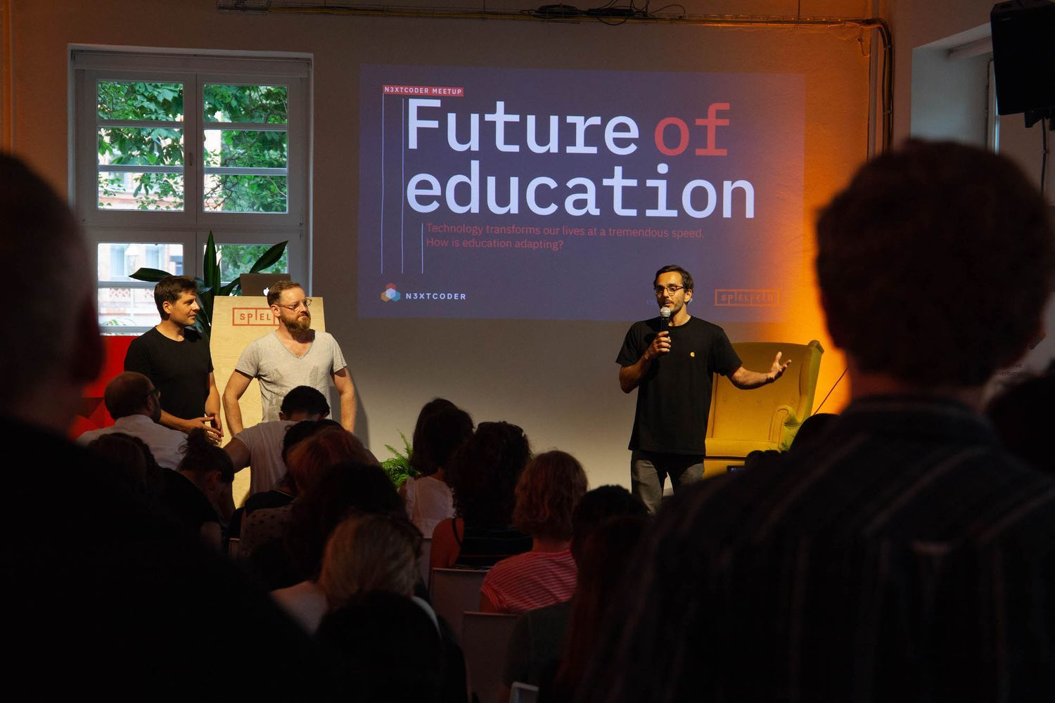 The Nextcoder founders Simon Stegemann, Jonathan Moore and Leonhard Nima standing in front of the future of education presentation.
