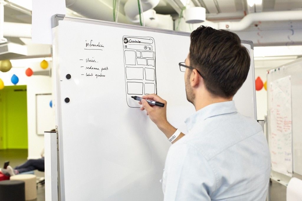 guy drawing a wireframe on a whiteboard